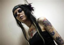 A woman displays her tattoo during an international tattoo exhibition in Budapest March 12,2011.  REUTERS/Laszlo Balogh