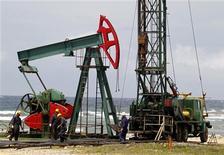 Рабочие следят за добычей нефти на окраине Гаваны, 10 июня 2011 года. Нефть показывает небольшое снижение во вторник утром на фоне легкого перевеса опасений о глобальном росте над фактором роста напряженности вокруг Ирана. REUTERS/Enrique De La Osa
