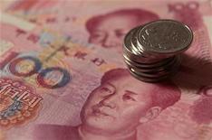 Монеты в один юань и банкноты в 100 юаней в Пекине, 30 декабря 2010 г.  Китай может и должен расширить дневной торговый диапазон своей валюты, но прежде чем юань станет полностью конвертируемым и свободно торгуемым, придется реформировать финансовый сектор, сказал во вторник советник Центробанка. REUTERS/Petar Kujundzic