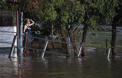 Женщина стоит у затопленного дома в городе Уогга-Уогга, 6 марта 2012 г. Более 13.000 человек на востоке Австралии были вынуждены во вторник покинуть свои дома из-за наводнения, вызванного рекордного количества дождей, которые привели к разливу рек и прорыва дамб в трех штатах. REUTERS/Daniel Munoz