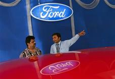 An employee speaks to a potential customers next to a Ford car inside the company's showroom in Mumbai March 3, 2012. Ford Motor Co will focus on small, low-cost cars in India to make the country a manufacturing hub for Africa and the Asia-Pacific region, the head of its Indian operations said, as it races to catch up with global rivals in the fast-growing market. Picture taken March 3, 2012.  REUTERS/Danish Siddiqui