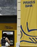Женщина снимает деньги в банкомате Piraeus bank в Афинах 15 июля 2010 года. Все банки Греции с гособлигациями на руках примут участие в программе реструктуризации долга страны, сообщили во вторник четыре источника в греческих банках. REUTERS/Yiorgos Karahalis