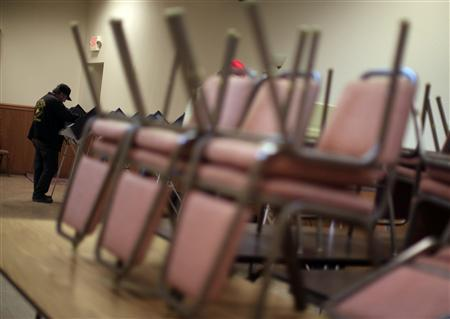 A voter looks over his ballot to place a vote at a polling station at the Knoxville Fire Department in Knox Township, Ohio, March 6, 2012. EUTERS/Jim Young