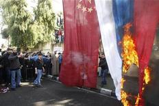 Сторонники сирийской оппозиции жгут российский и китайские флаги на акции протеста в Ливане 10 февраля 2012. Китай отзывает домой своих рабочих из Сирии, памятуя о ситуации прошлого года, когда Пекину пришлось экстренно эвакуировать своих граждан из охваченной боями Ливии. REUTERS/Ali Hashisho