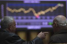 Traders talk in front of a screen showing an index at Madrid's Bourse February 14, 2012. REUTERS/Sergio Perez