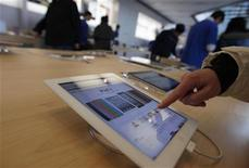 A customer tests out an Apple iPad at an Apple Store in downtown Shanghai February 28, 2012.  REUTERS/Carlos Barria