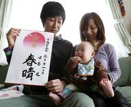 Hiromi Sato holds her son, Haruse, as her husband, Kenji Sato, holds a calligraphy with the characters of his son's name and the date he was born during a photo opportunity at their home in Minamisanriku, northeastern Japan, March 3, 2012.  REUTERS/Yuriko Nakao
