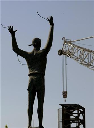 A statue of Greek marathon runner Spyros Louis showing him crossing the finish line of a marathon race is seen next to cranes placed around the Athens' Olympic complex. REUTERS/Yiorgos Karahalis