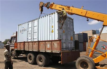 A worker climbs a container to release the crane clamp after it was loaded onto a supply truck at Thar Dry Port in Sanand, in Gujarat October 3, 2011. REUTERS/Amit Dave/Files