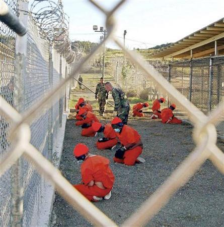 Detainees sit in a holding area during their processing into the temporary detention facility, as they are watched by military police, at Camp X-Ray inside Naval Base Guantanamo Bay in this January 11, 2002 file photograph. McCoy/Handout/Files/Files
