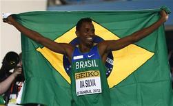 Mauro Vinícios da Silva segura a bandeira brasileira depois de ganhar neste sábado a medalha de ouro no salto em distância no Campeonato Mundial Indoor de Atletismo, em Istambul, na Turquia. 10/03/2012 REUTERS/Kai Pfaffenbach