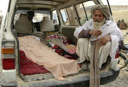 An elderly Afghan man sits next to the covered bodies of people who were killed by coalition forces in Kandahar province, March 11, 2012. REUTERS/ Ahmad Nadeem