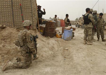 U.S. soldiers keep watch at the entrance of a U.S. base in Panjwai district Kandahar province, March 11, 2012. REUTERS/ Ahmad Nadeem