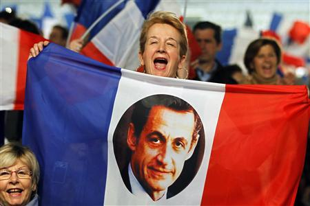 A supporter of French President Nicolas Sarkozy, candidate for the 2012 French presidential election, holds the national flag with a picture of him as she reacts during a campaign rally in Villepinte, northern Paris March 11, 2012. REUTERS/Charles Platiau