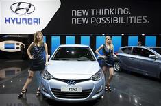 Hostesses stand next to a Hyundai i20 model car displayed on the car maker's booth during the first media day of the Geneva Auto Show at the Palexpo in Geneva, March 6, 2012. REUTERS/Valentin Flauraud
