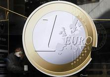 Мужчина обедает в кафе с логотипом единой европейской валюты в Мадриде, 9 декабря 2011 года. Экономика еврозоны показывает предварительные признаки улучшения, согласно последнему ежемесячному отчету Организации экономического сотрудничества и развития (ОЭСР), опубликованному в понедельник. REUTERS/Susana Vera