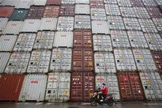 A woman rides her motorcycle past shipping containers at the Port of Shanghai February 10, 2011. REUTERS/Aly Song