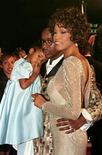 """A atriz e cantora Whitney Houston posa com seu marido Bobby Brown e sua filha Bobbi Kristina na estreia de seu filme """"Cinderella"""", 13 de outubro de 1997. REUTERS/Str Old"""