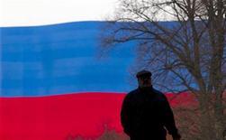 Мужчина идет по центру Москвы на фоне флага России 6 марта 2012 года. Федеральный бюджет РФ в январе-феврале 2012 года был исполнен с дефицитом в размере 245,3 миллиарда рублей, или 3,0 процента ВВП, сообщил Минфин РФ во вторник. REUTERS/Thomas Peter
