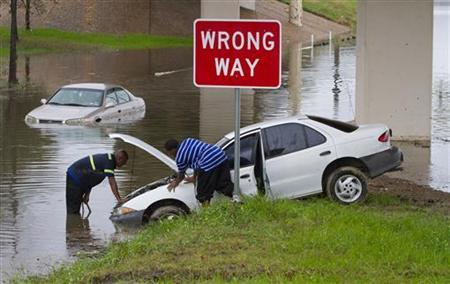 Lewis Crawford (R) gets some help from wrecker driver Terrance Lezama after his vehicle was stranded by freeway flooding as heavy rains hit Houston, Texas January 9, 2012. REUTERS/Richard Carson