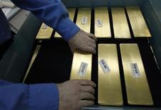 Рабочий готовит к маркировке золотые слитки на заводе Красцветмет в Красноярске 28 марта 2011 года. Российская золотодобывающая компания Полюс Золото увеличила доказанные и вероятные запасы на 12 процентов до 90,5 миллиона тройских унций, сообщила компания в среду. REUTERS/Ilya Naymushin