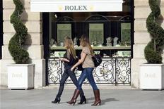 Women walk past a window display of luxury goods maker Rolex in Paris' Place Vendome October 13, 2008. REUTERS/Charles Platiau