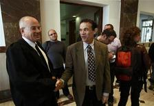 Israeli antiquities collector Oded Golan shakes hands with his lawyer Lior Bringer (L) after he was acquitted by Jerusalem District Court March 14, 2012. REUTERS/Ronen Zvulun