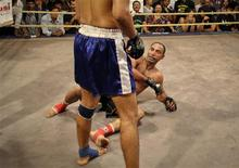Amjad Khan, a 30-year-old mixed martial arts fighter, falls down during a bout at a fight night in Mumbai February 25, 2012. First started around three years ago by Full Contact Championship (FCC), a company founded to promote mixed martial arts, fight nights are slowly gaining popularity in India, a nation where people traditionally have had no inclination to pay money to watch somebody be physically beaten in front of them. But increasing globalisation, and years of growing up watching overseas professional wrestling broadcasts, have given younger Indians a taste for seeing the real thing themselves. Picture taken February 25, 2012. To match story INDIA-FIGHTNIGHT/ REUTERS/Danish Siddiqui