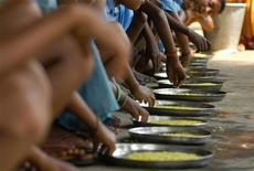 """Children eat food at an """"anganwadi"""" (creche) centre under the Integrated Child Development Services (ICDS) scheme in Gandhi village, about 45 km (28 miles) west of the northeastern Indian city of Agartala, April 9, 2009. REUTERS/Jayanta Dey"""