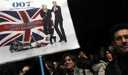 """Employees of Spanish airline Iberia wait for the start of a demonstration in Madrid January 19, 2012. Iberia workers claim that the management's plans to create the low-cost air carrier Iberia Express will threaten their jobs and working conditions. The banner depicts Iberia chairman Antonio Vazquez (L) and Iberia CEO Rafael Sanchez as secret agents in the James Bond movie """"On Her Majesty's Secret Service"""". REUTERS/Susana Vera"""