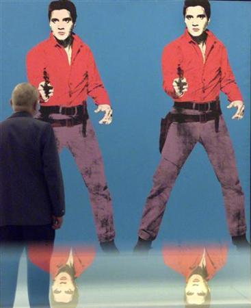 A unidentified man watches the artwork ''Elvis I and II'' by U.S. pop artist Andy Warhol in Berlin October 5, 2001. REUTERS/Alexandra Winkler