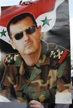 Мужчина держит плакат с изображением президента Сирии Башара Асада во время демонстрации в Дамаске, 15 марта 2012 года. Башар Асад всегда говорил, что Сирия изменится. REUTERS/Khaled al-Hariri