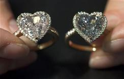 A model wears a pair of fancy coloured heart-shaped diamond rings during an auction preview at Christie's in Geneva May 7, 2010. REUTERS/Denis Balibouse