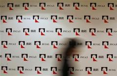 Женщина проходит мимо доски с логотипами Русала в Гонконге, 11 января 2010 года. Новым главой совета директоров алюминиевого гиганта Русал избран Барри Чьюнг, который до этого входил в состав совета, сказал Рейтер источник, близкий одному из акционеров. REUTERS/Bobby Yip