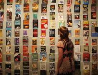 Женщина смотрит обложки книг про Джеймса Бонда на выставке в Лондоне, 16 апреля 2008 года. Обладатель прав на произведения Яна Флеминга подписал 10-летнее соглашение с Random House Group о публикации книг о Джеймсе Бонде в печатном и электронном виде, сообщил в пятницу издатель. REUTERS/Stephen Hird