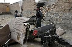 Афганский полицейский стоит у обломков вертолета в Кабуле, 16 марта 2012 г. Двенадцать турецких солдат и четыре мирных жителя погибли в результате падения вертолета НАТО на дом на окраине Кабула, сообщили турецкие военные и представитель афганской полиции. REUTERS/Mohammad Ismail