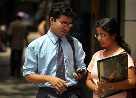 Students look at a text message from a mobile phone in Kolkata, August 23, 2005. REUTERS/Jayanta Shaw/Files