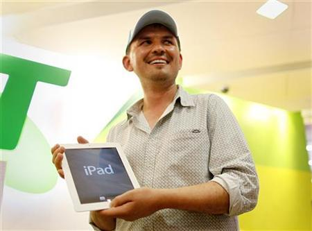 Construction manager David Tarasenko poses with the first new iPad from a store in Sydney, moments after midnight, March 16, 2012. Apple Inc's new iPad went on sale in Australia early on Friday, greeted by throngs of fans hungry to get hold of the U.S. consumer giant's latest, 4G-ready tablet computer. REUTERS/Tim Wimborne