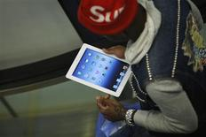 A customer checks his new iPad after purchasing it at a department store in Manhattan, New York, shortly after the 4G-ready tablet computer went on sale at midnight March 16, 2012. REUTERS/Eduardo Munoz