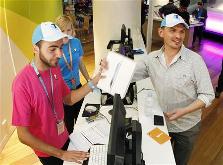 Construction manager David Tarasenko (R) purchases the first new iPad from a store in Sydney, moments after midnight, March 16, 2012. Apple Inc's new iPad went on sale in Australia early on Friday, greeted by throngs of fans hungry to get hold of the U.S. consumer giant's latest, 4G-ready tablet computer. REUTERS/Tim Wimborne