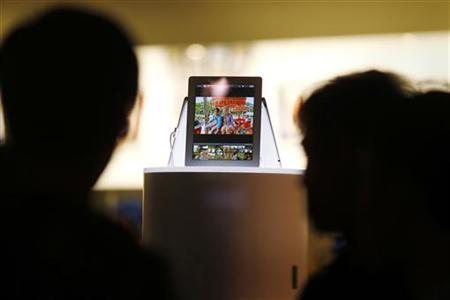 Passers-by look at a new iPad in a window display in an Apple store in Sydney March 15, 2012. Apple Inc's new iPad went on sale in Australia early on Friday, greeted by throngs of fans hungry to get hold of the U.S. consumer giant's latest, 4G-ready tablet computer. REUTERS/Tim Wimborne