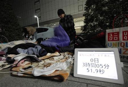 Dai Shimazaki folds his sleeping bag after waking up on a street in front of an Apple store as he waits for the sales of the new iPad in Tokyo March 16, 2012. Apple's new iPad uses chips made by Qualcomm , Broadcom, Samsung Electronics and other semiconductor makers, according to repair firm iFixit, which cracked open one of the devices. He had waited for the sale on the street since Wednesday night. The iPad's screen shows the countdown for the sales. REUTERS/Kim Kyung-Hoon