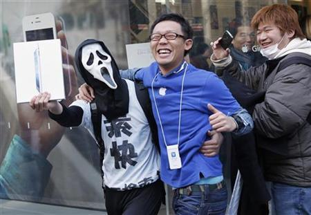 A man in a mask celebrates with Apple store's staff after purchasing new iPad at its Ginza store in Tokyo March 16, 2012. Apple's new iPad went on a sale in Japan on Friday and more than 450 people waited on the line to purchase the new device in front of the shop prior to its opening. REUTERS/Kim Kyung-Hoon