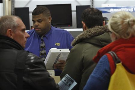 A departmental store worker releases one unit of Apple's new iPad to a customer in Manhattan, New York, shortly after the 4G-ready tablet computer went on sale at midnight March 16, 2012. REUTERS/Eduardo Munoz