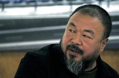 """Dissident Chinese artist Ai Weiwei talks to members of his staff as he sits in his studio in Beijing, in this November 15, 2011 file photo. For nearly two hours on Sunday, dissident artist Ai Weiwei was able to maintain a Twitter-like microblog account, briefly raising hopes the Chinese government had relaxed some of its tight control over online expression. Ai's first microblog post said: """"Testing. Ai Weiwei. March 18, 2012."""" REUTERS/David Gray/Files"""