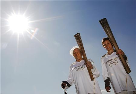 The Oldest Olympic torch bearer for the London 2012 Olympic Games, Dinah Gould (L) who will be 100 when she carries the flame, and the youngest, 11 year old Dominic John MacGowan, pose for a photograph with Olympic torches during a photo-call at Stepney Green Park in London March 19, 2012.  REUTERS/Luke MacGregor