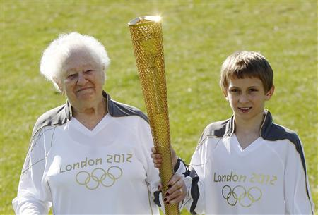The Oldest Olympic torch bearer London 2012 Olympic Games, Dinah Gould (L) who will be 100 when she carries the flame, and the youngest, 11 year old Dominic John MacGowan, pose for a photograph with Olympic torches during a media viewing at Stepney Green Park in London March 19, 2012. REUTERS/Luke MacGregor