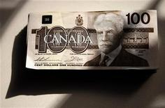 Canadian one hundred dollar bills are displayed in this posed photograph in Toronto, October 22, 2008. REUTERS/Mark Blinch