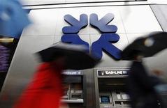Люди проходят мимо отделения банка Royal Bank of Scotland (RBS) в Лондоне, 4 ноября 2011 года. Второй по величине банк Великобритании Royal Bank of Scotland закрывает бизнес по обслуживанию рынков инвестиционного капитала и корпоративных финансов в Южной Корее, а также брокерского обслуживания на фондовых рынках в Индонезии, Сингапуре и Корее, согласно служебной записке, попавшей в распоряжение Рейтер во вторник. REUTERS/Andrew Winning