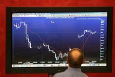 Трейдер изучает график на экране в зале ММВБ в Москве, 23 мая 2006 г. Коррекция, которая началась на российском рынке акций накануне, продолжается во вторник, и на этот раз движение совпадает с динамикой мировых фондовых площадок и цены на нефть. REUTERS/Alexander Natruskin